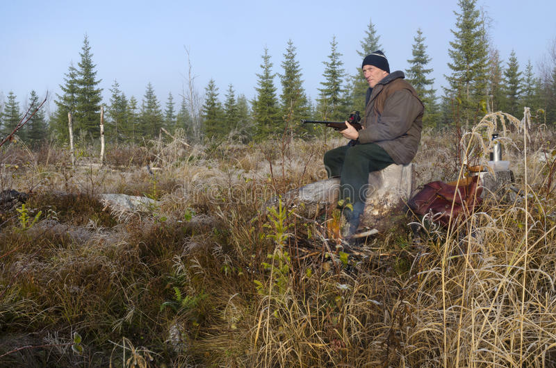 Swedish Hunter. Moose hunter sitting on a stump with a litle fire in front holding his rifle pointing forward, picture from the North of Sweden stock photography