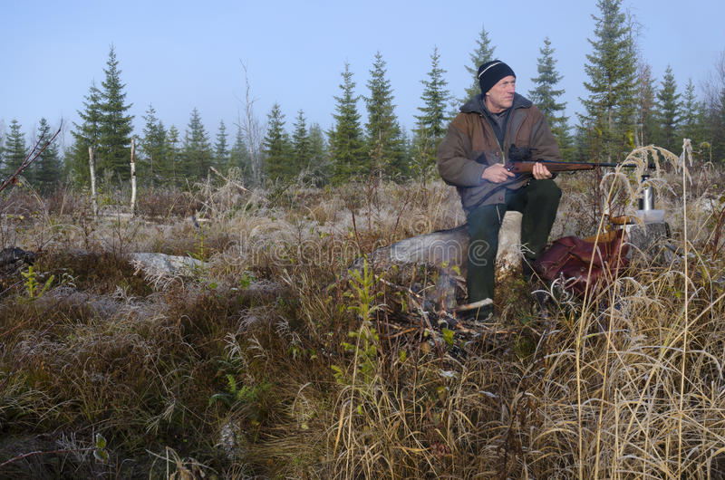 Swedish Hunter. Moose hunter sitting on a stump with a litle fire in front holding his rifle pointing to the left, picture from the North of Sweden stock images