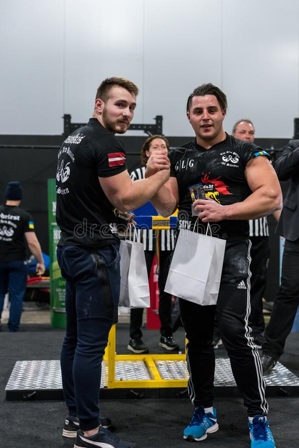 A Swedish and Latvian male arm wrestler in price award ceremony. STOCKHOLM, SWEDEN - JANUARY 13, 2018: A swedish and Latvian male armwrestler getting a price at royalty free stock photo