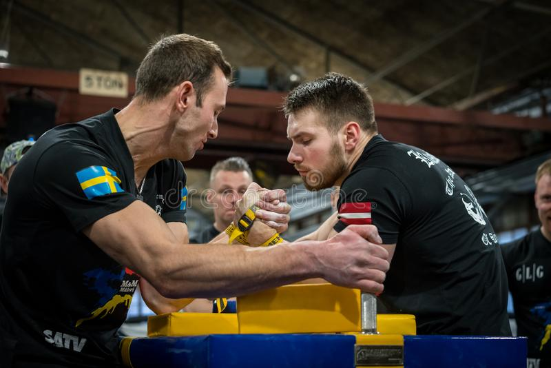 A Swedish and Latvian male arm wrestler in a tough fight. STOCKHOLM, SWEDEN - JANUARY 13, 2018: Profile view of a Swedish and Latvian male arm wrestler in a royalty free stock image