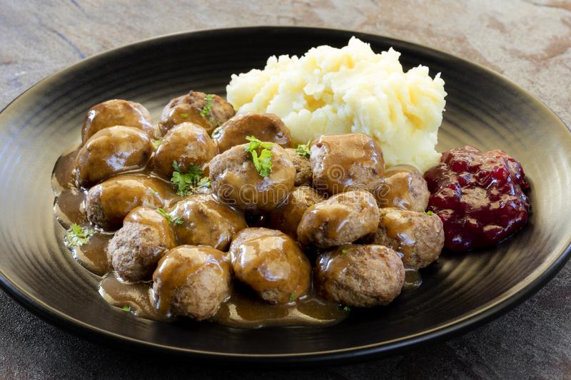Swedish Meatballs with Lingonberry on Black Plate over Slate. Swedish meatballs with mashed potatoes, gravy and lingonberry on black plate. Side view, over slate stock images