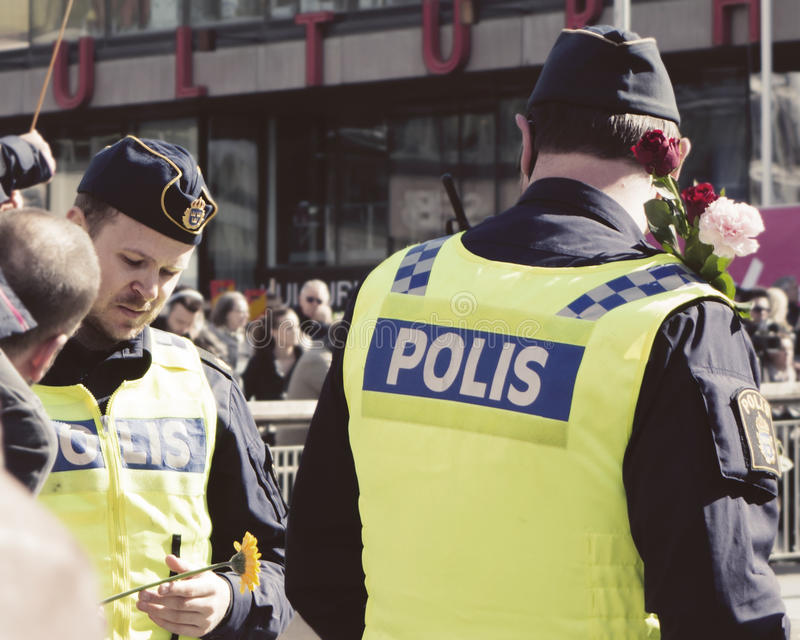 Swedish police receiving flowers after the terror attack. After the terror attack in central Stockholm people are showing appreciation and giving flowers to the stock photography