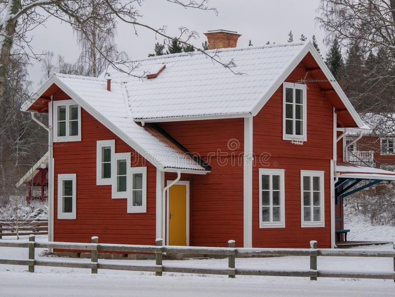 Swedish red two storeywooden family houses behind a snow covered tree alongside the snow surfaced road in the residential area stock images