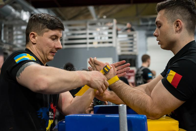 A Swedish and Romanian male arm wrestler preparing for a fight. STOCKHOLM, SWEDEN - JANUARY 13, 2018: Profile view of a Swedish and Romanian male arm wrestler stock image