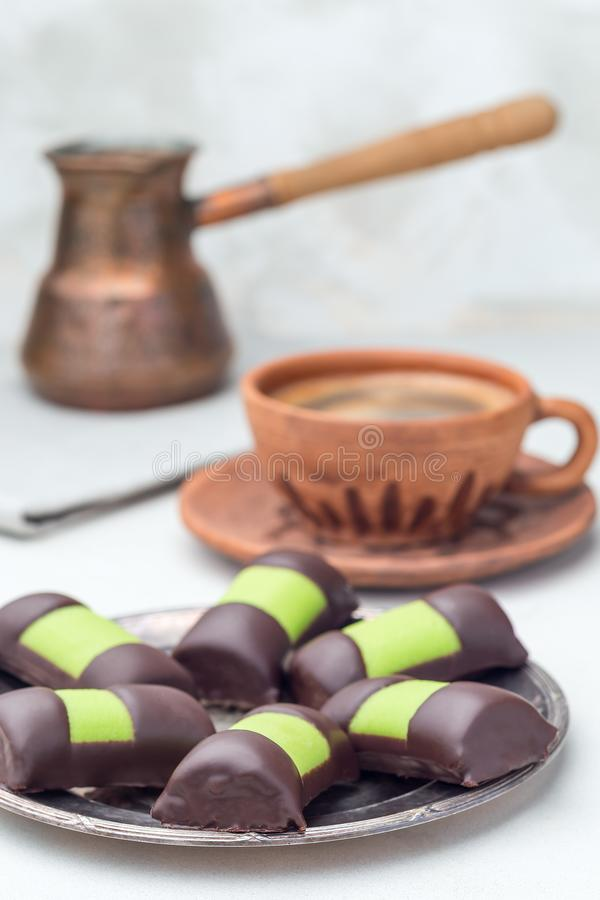 Swedish sweets punsch rolls or punschrullar, covered with green marzipan, on metall plate, served with coffee,  vertical. Swedish sweets punsch rolls or stock image
