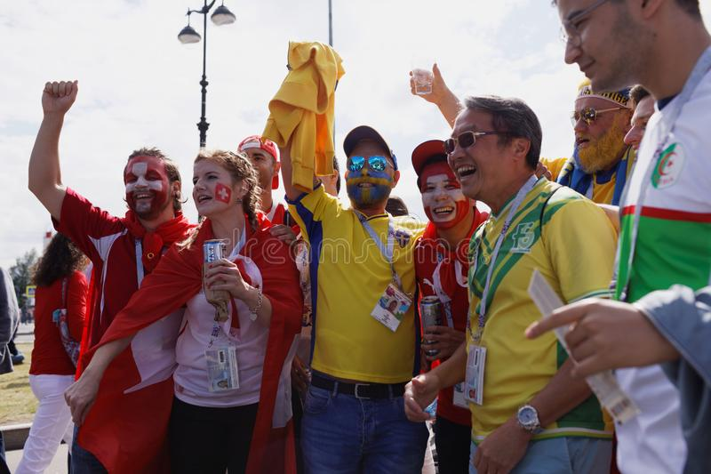 Swedish and Swiss football fans in Saint Petersburg, Russia during FIFA World Cup 2018. St. Petersburg, Russia - July 3, 2018: Swedish and Swiss football fans at royalty free stock image
