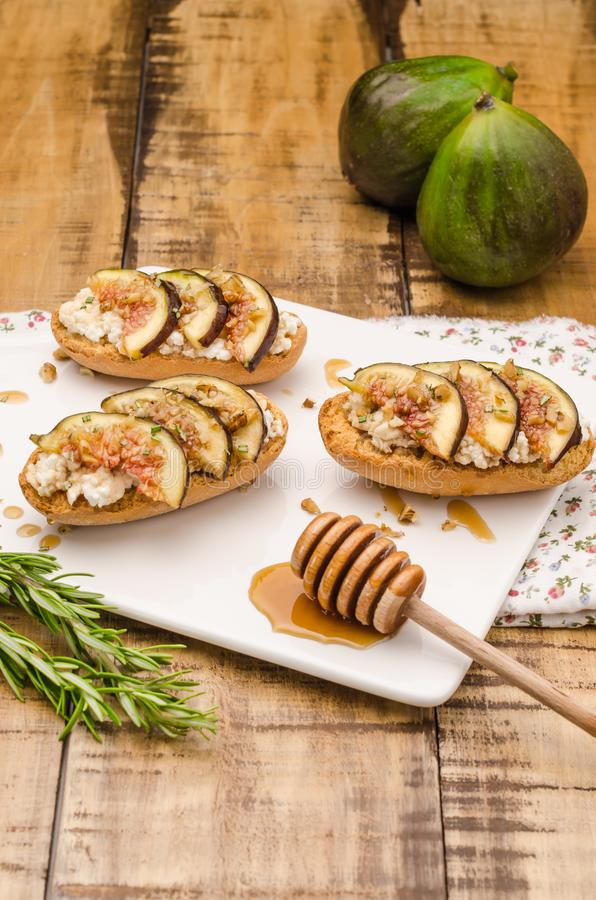 Swedish toasts with figs, cheese, rosemary, honey and walnuts royalty free stock photo