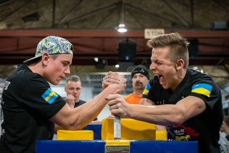A Swedish and Ukrainian arm wrestler in a tough fight. STOCKHOLM, SWEDEN - JANUARY 13, 2018: Profile view of a Swedish and Ukrainian male arm wrestler in a royalty free stock images