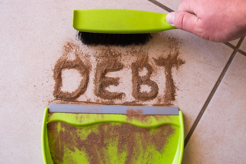 Sweep Debt Clean Concept. With debt written in dirt on a floor and a person is about to sweep the debt dirt in a dust pan using a small hand broom royalty free stock photography