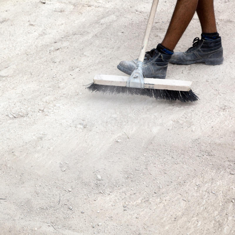Sweeping. A person sweeping with a push broom stock images