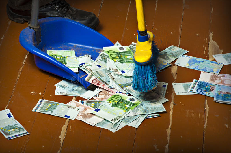 Sweeping euro money banknotes. Person sweeping euro money banknotes with a broom to scoop stock image
