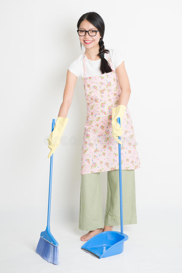 Sweeping floor. Full length Asian Chinese female housekeeping, sweeping floor with broom on plain background stock image