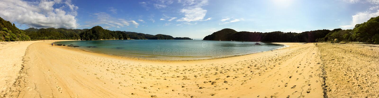 A sweeping panoramic view of  a beautiful golden beach and cove in Able Tasman National Park, New Zealand. Against a bright blue sky royalty free stock images