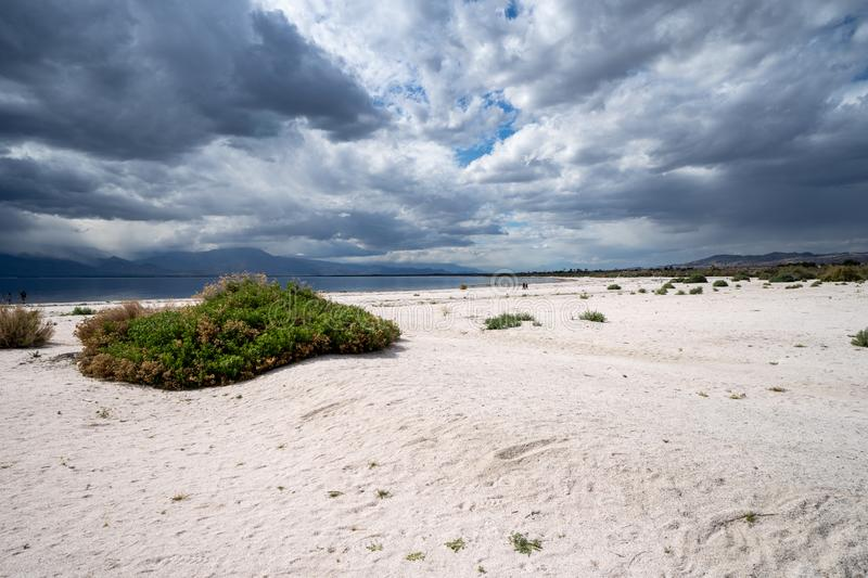 Sweeping, wide angle view of the decaying beach at the Salton Sea in California, as storm clouds roll in stock image