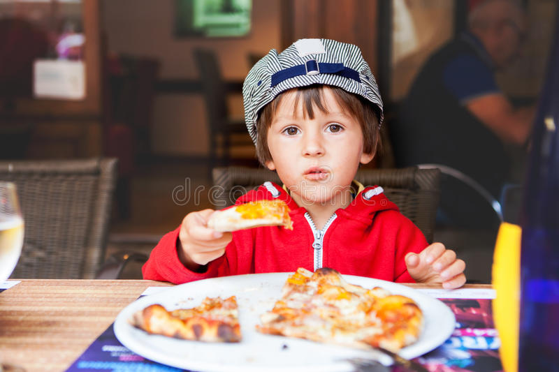 Sweet adorable child, boy, eating pizza at a restaurant stock photography