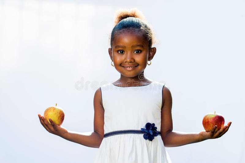 Sweet african girl holding apple in each hand. royalty free stock photography