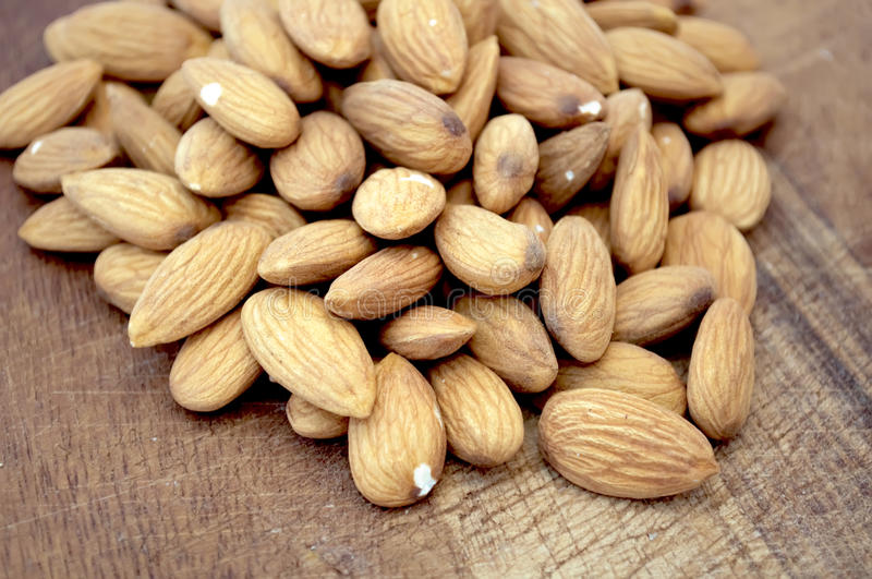 Sweet Almonds. A pile of sweet almonds on a wooden breadboard stock photo