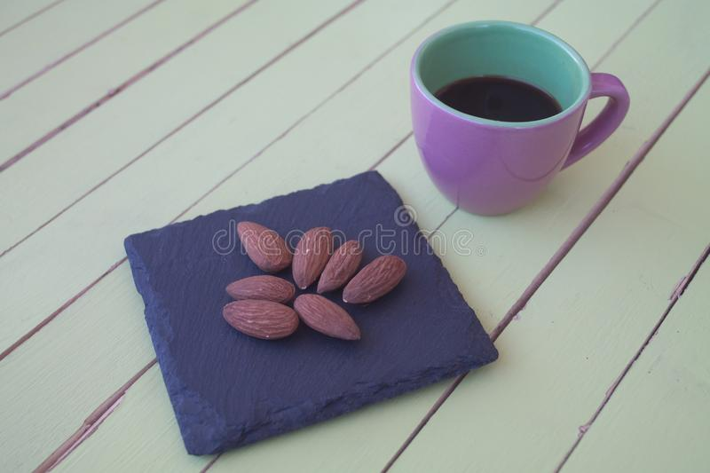 Sweet almonds on a slate plate and coffee on green wood royalty free stock image