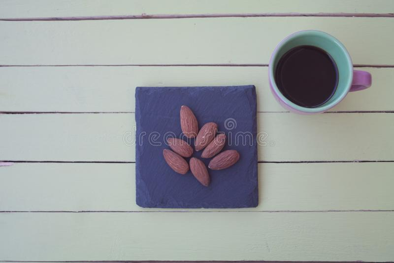 Sweet almonds on a slate plate and coffee on green wood from above royalty free stock images