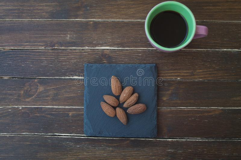 Sweet almonds on a slate plate and coffee on wood from above stock photography