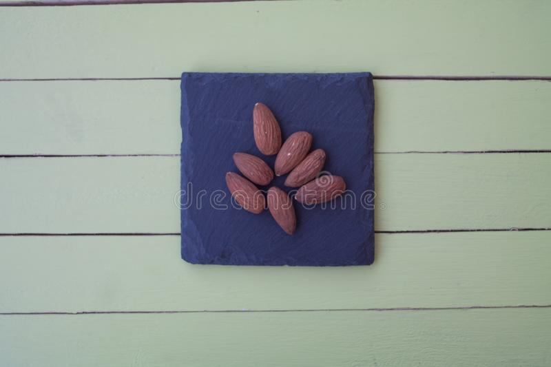 Sweet almonds on a slate plate on green wood from above stock image