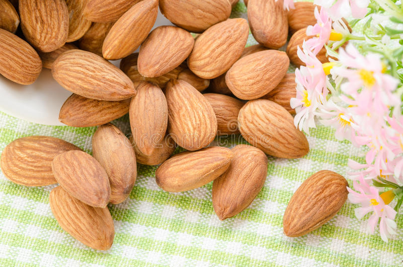 Sweet almonds in white cup with flower. royalty free stock images