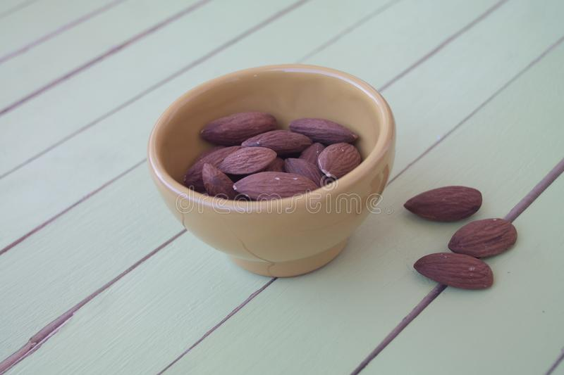 Sweet almonds in a yellow bowl on green wood royalty free stock photo