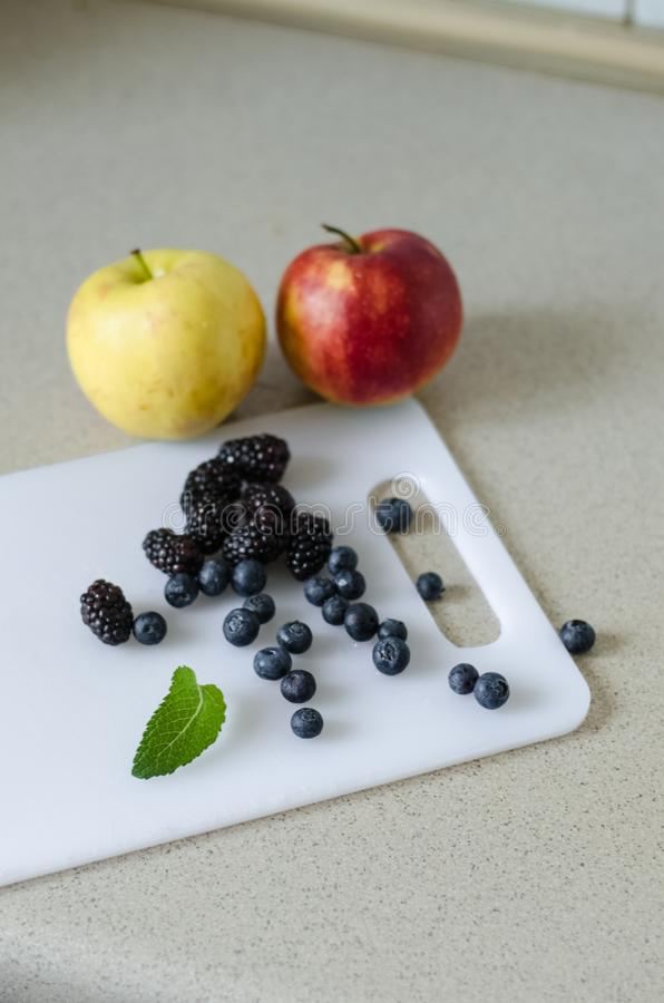 Sweet apples, blueberries, blackberries and mint leaves around, fresh summer fruits from market royalty free stock images