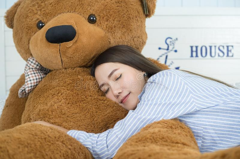 Asian girl sleeping on the bed with a big brown teddy bear. Sweet Asian girl sleeping on the bed with a big brown teddy bear stock images