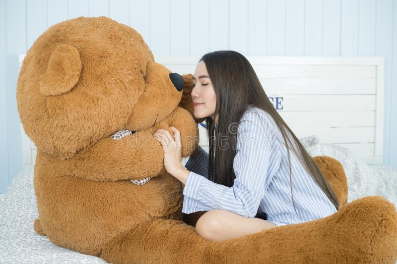 Asian girl sleeping on the bed with a big brown teddy bear. Sweet Asian girl sleeping on the bed with a big brown teddy bear royalty free stock photos
