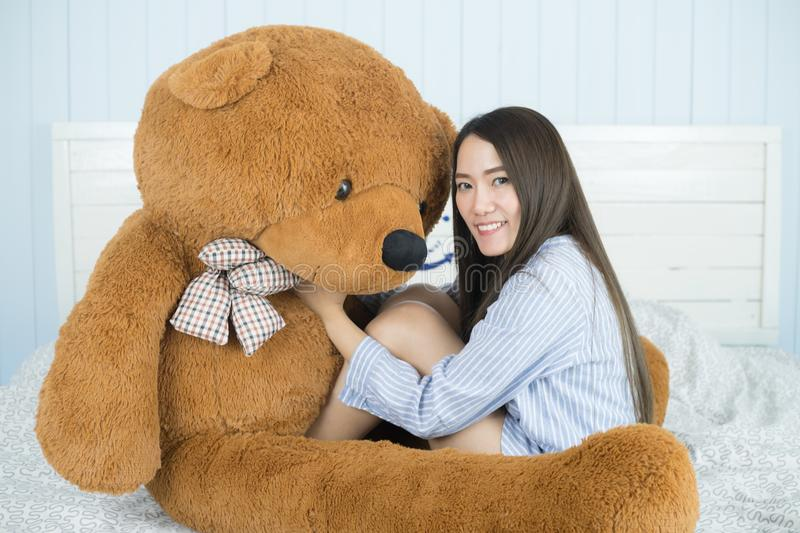 Asian girl sleeping on the bed with a big brown teddy bear. Sweet Asian girl sleeping on the bed with a big brown teddy bear stock photo