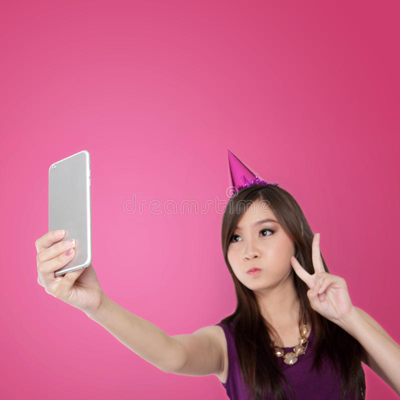 Sweet Asian teen doing a cute selfie pose. Sweet Asian teenage girl making victory hand sign with cute face expression while taking a self shot picture with her royalty free stock photography