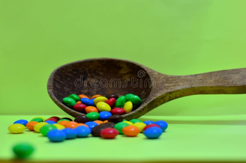 Sweet assorted multicolored chocolates, gum balls in a wooden spoon on a green photon or tablets and vitamins. royalty free stock photo