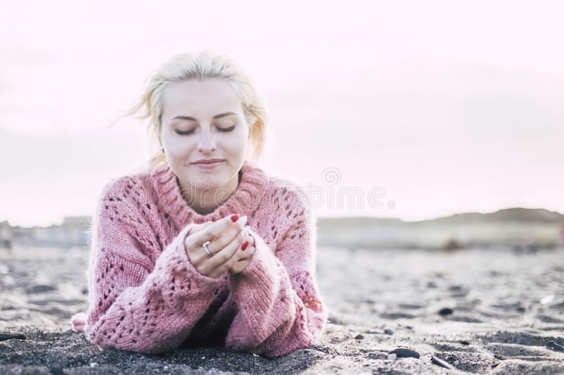 Sweet attractive cheerful and thoughtful blonde yong woman lay down at the beach on the sand to enjoy the freedom and the leisure stock image