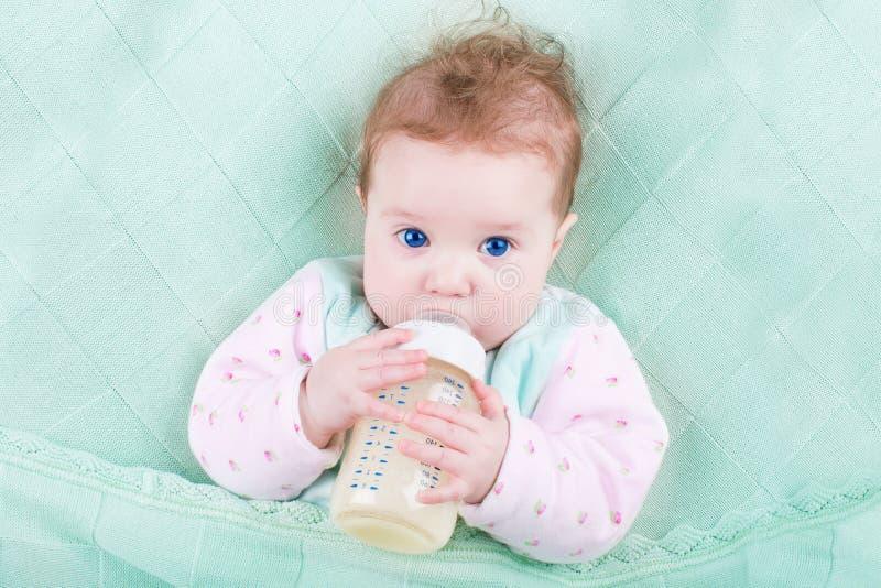 Sweet baby with big blue eyes drinking milk stock image