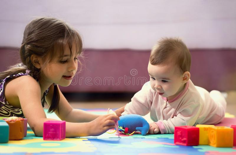 Sweet Baby Boy and Elder Child Sister Playing With Toys royalty free stock images