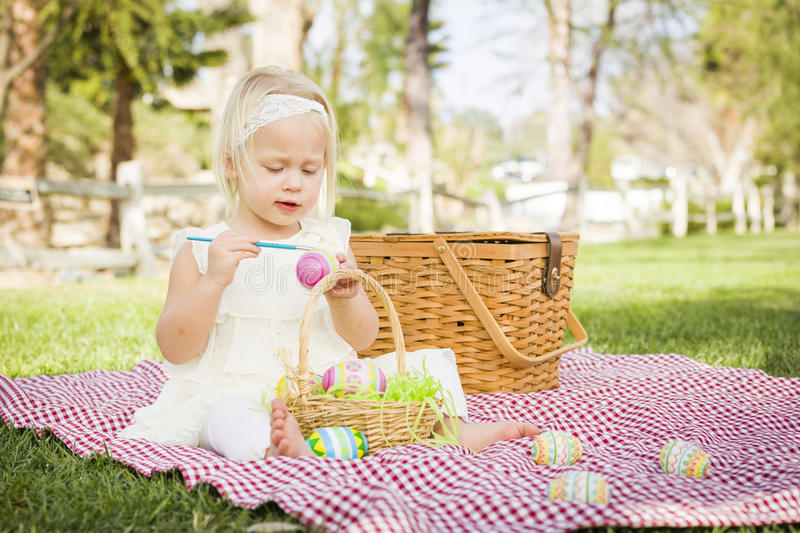 Sweet Baby Girl Coloring Easter Eggs on Picnic Blanket royalty free stock images