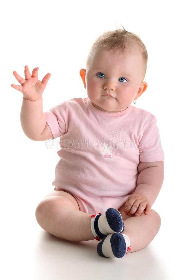 Sweet baby girl sitting and waving arm royalty free stock images