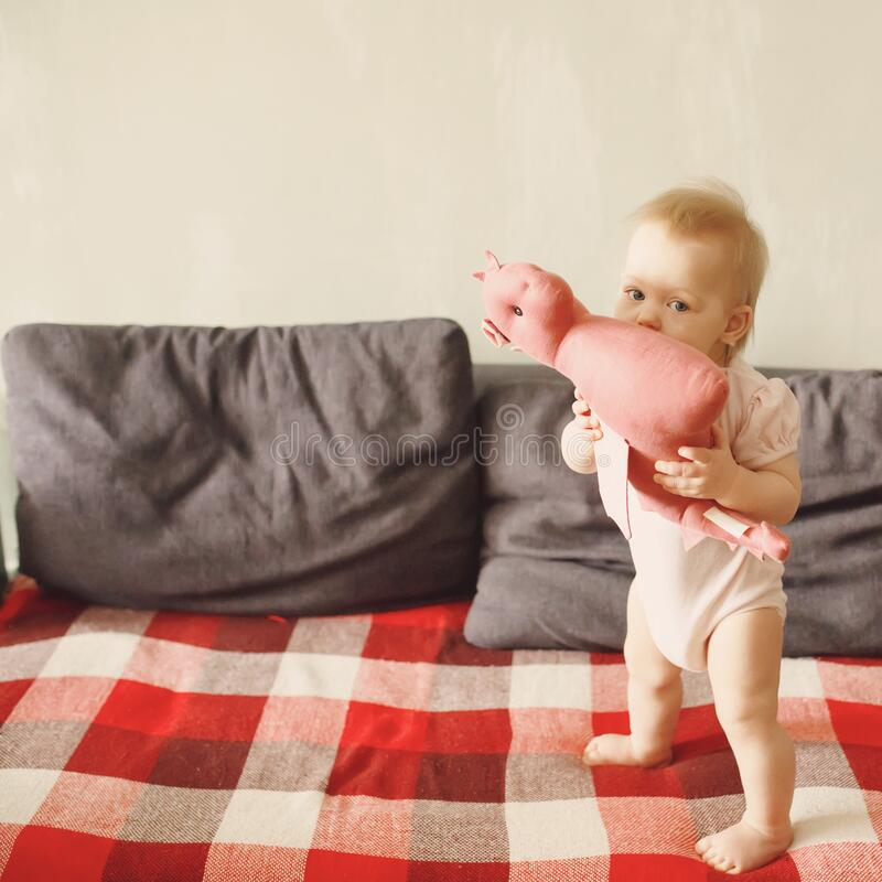 Sweet baby girl standing on her little feet on a couch at home, playing. With her soft dragon toy, looking at camera, full height stock image