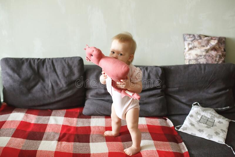Sweet baby girl standing on her little feet on a couch at home, playing. With her soft dragon toy, looking at camera, full height royalty free stock images