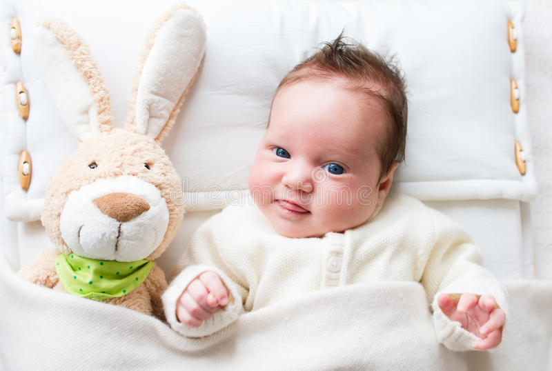 Sweet baby girl in a white crib with bunny toy. Sweet little baby girl in a white crib with bunny toy stock photography