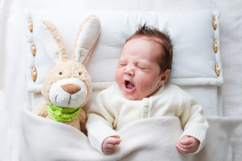 Sweet baby girl in a white crib with bunny toy. Sweet little baby girl in a white crib with bunny toy royalty free stock photos