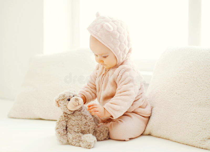 Sweet baby playing with teddy bear toy at home in white room. Near window royalty free stock image
