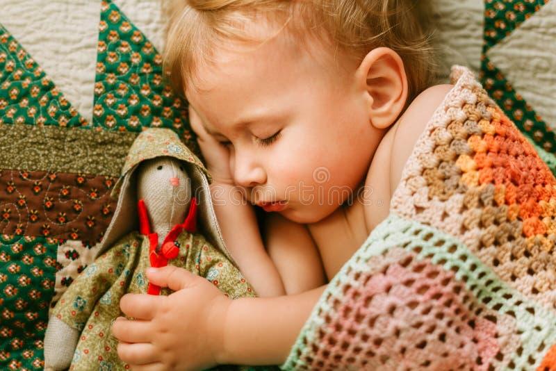 Sweet Baby schlafen mit Spielzeug in Händen stockfotografie