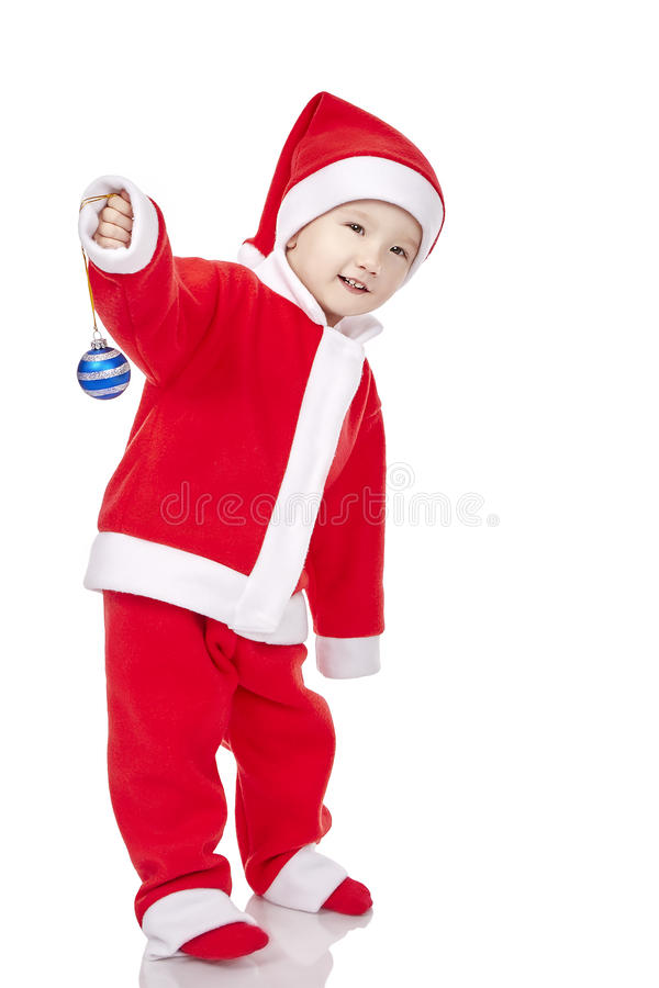 Sweet baby wearing a Santa costume, smiling and holding a small stock image