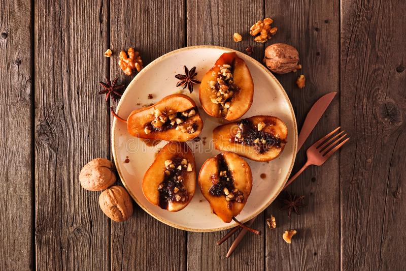 Sweet baked autumn pears, top view over rustic wood with frame of ingredients royalty free stock photos