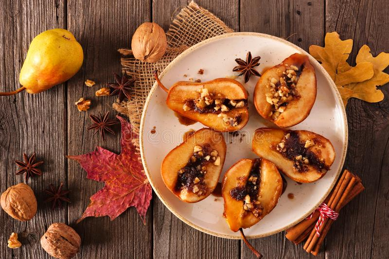 Sweet baked autumn pears, top view table scene over rustic wood royalty free stock image