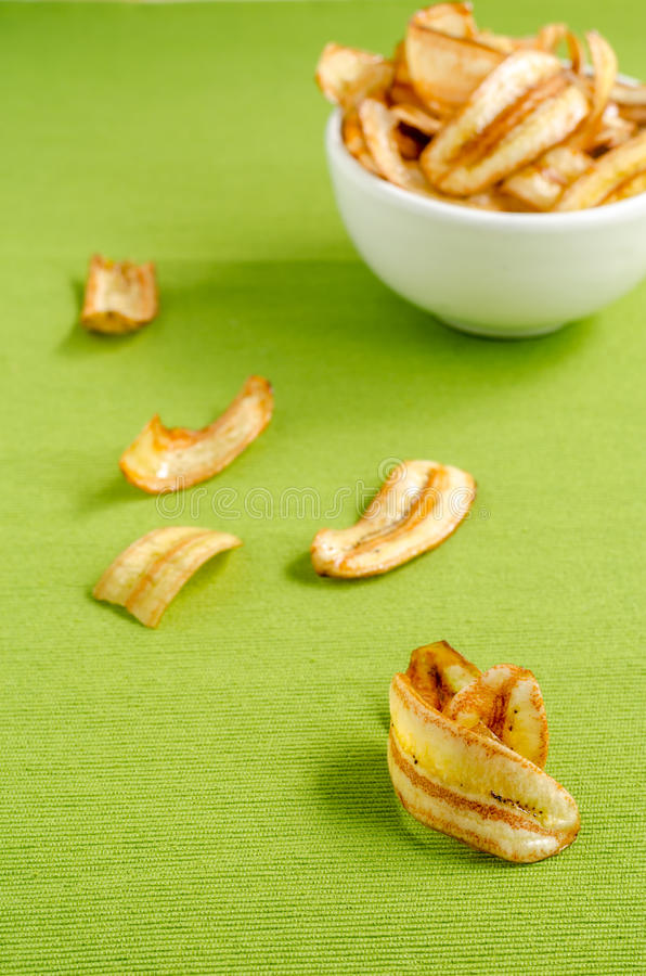 Sweet banana chips on green tablecloth background.  stock photography