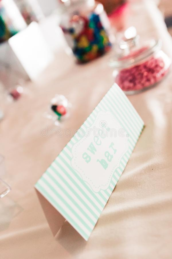 Sweet Bar Paper Sign on Wedding Table with Coloured Sweets stock photo