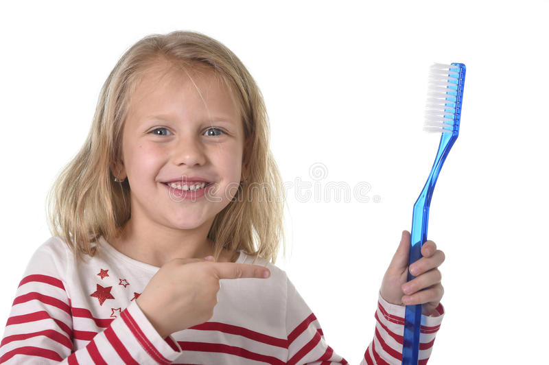 Sweet beautiful female child with blond hair and big blue eyes holding huge toothbrush smiling happy royalty free stock images